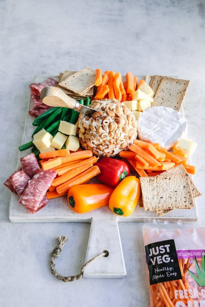 Grazing board or dinner platter with cheese ball, carrot sticks, meats and capsicums.